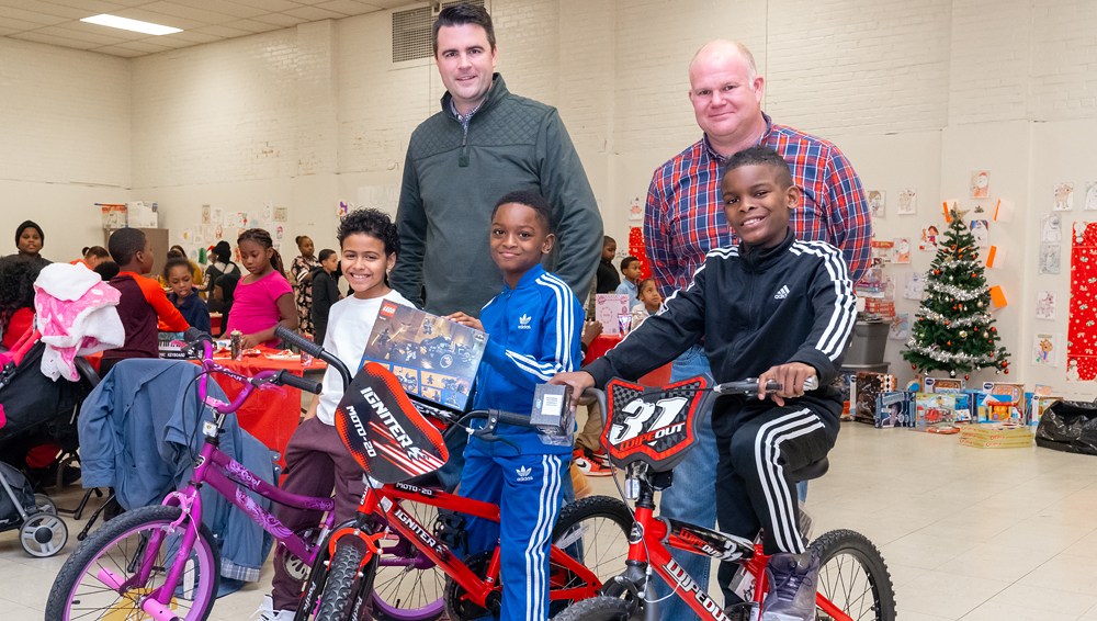 PSEG executives pose behind happy children who just received bicycles for Christmas