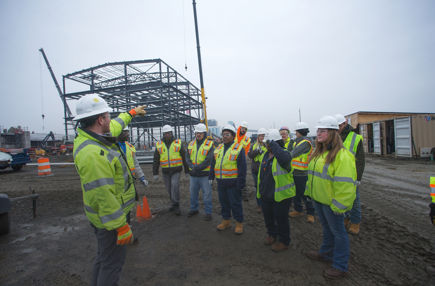 A group of students wearing hard hats and safety gear on a construction site being led by their instructor.