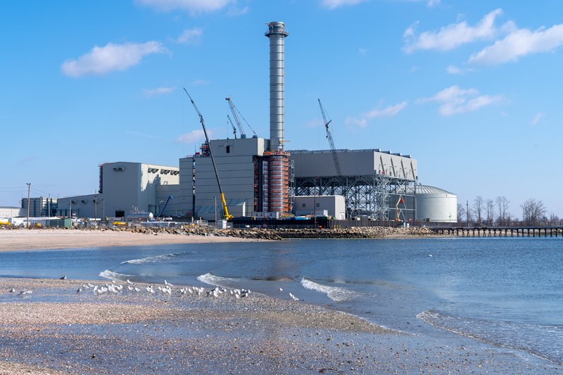 A silver combined-cycle power plant looms high near Seaside Park in Bridgeport
