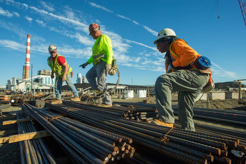 Union workers organizing steel rods at a construction site