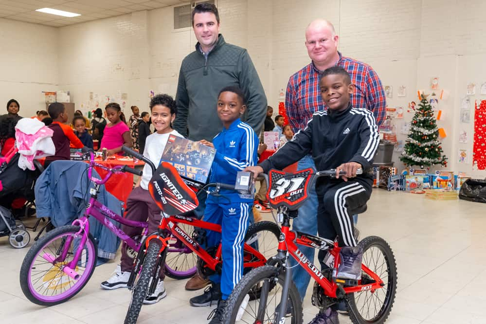 Jim Gilroy and Scott Sargent of PSEG pose with children on bikes during a toy drive at Marina Village